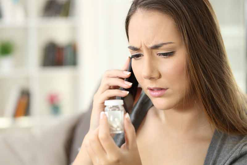 Dame kigger på glas med medicin
